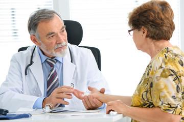 Arzt untersucht verletzte Hand der Patientin