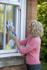 A mature woman cleaning windows of a house