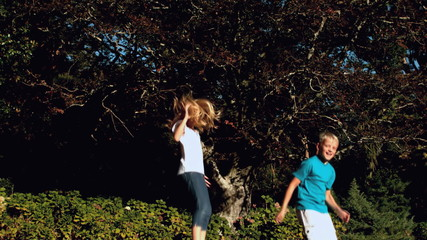 Cheerful siblings bouncing on a trampoline