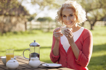 A mature woman having breakfast in a garden