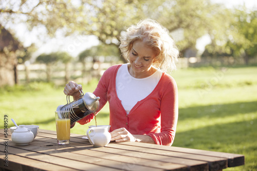 A mature woman having breakfast outside