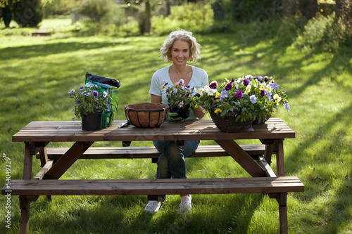 A mature woman planting hanging baskets