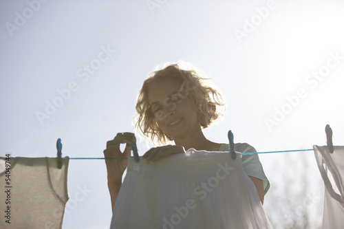 A mature woman pegging out washing on a washing line, front view