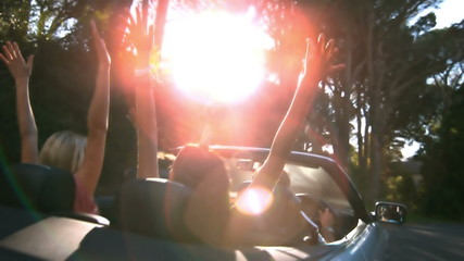Friends raising their hands in the air while man is driving