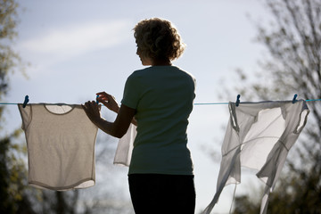 A mature woman pegging out washing on a washing line, rear view