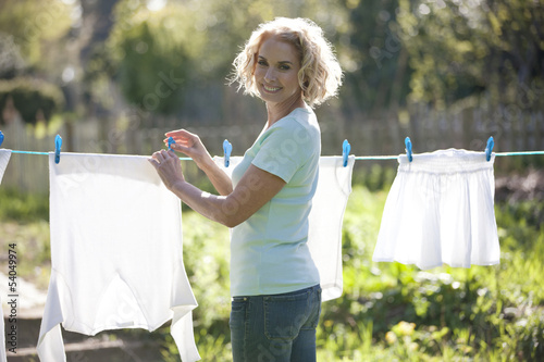 A mature woman pegging out washing on a washing line, smiling