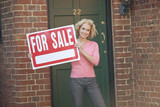 A mature woman holding a property for sale sign