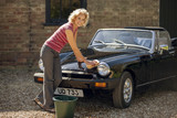 A mature woman washing a classic sports car