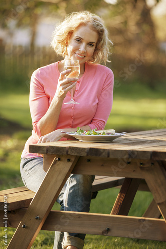 A mature woman eating a meal