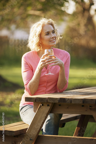 A mature woman drinking a glass of wine