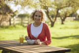 A mature woman sitting at a garden bench eating breakfast