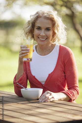 A mature woman sitting at a garden bench drinking orange juice