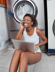 Woman Using Laptop And Mobilephone In Laundromat