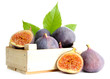 Ripe sweet figs with leaves in wooden crate isolated on white