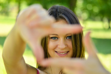 Beautiful girl making frame with hands while outdoors