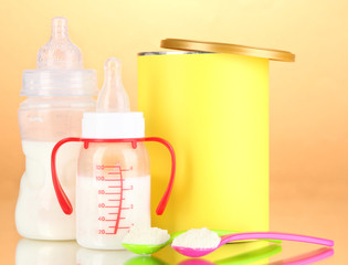 Bottles with milk and food for babies on beige background