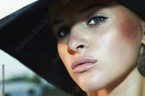 close-up portrait of beautiful woman in hat. green eyes