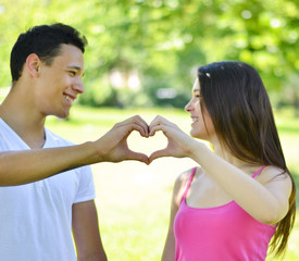 Couple making heart with hands outdoor