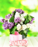 Beautiful lilac flowers, on wooden table on bright  background