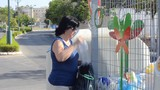 Woman throwing away plastic bottles into recycling container