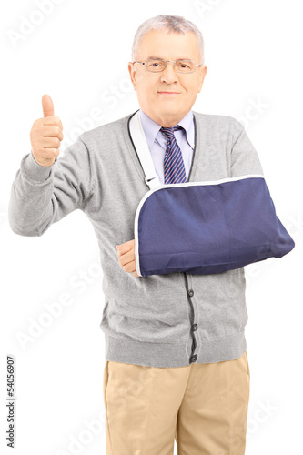 Senior man with broken arm giving thumb up