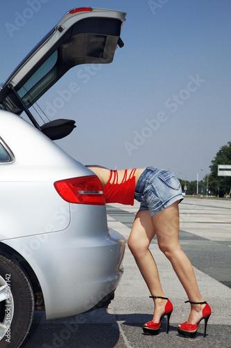 Frau im Kofferraum mit sexy Po und Beine