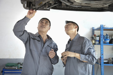 Two Mechanics Looking at Underside of a Car
