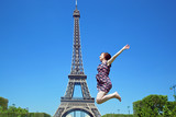 Young attractive jumping against Eiffel Tower, Paris, France