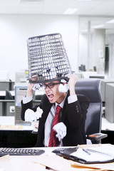 Angry businessman hold rubbish bin on his head at office