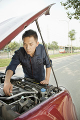 Mechanic Fixing Car by Roadside