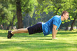Young handsome sportsman exercising in a park