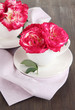 Roses in cups on napkin on wooden background