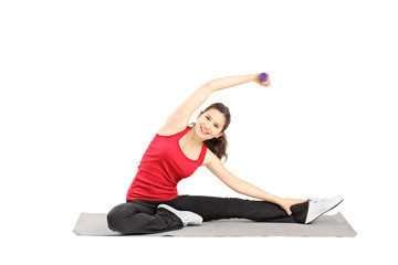 Young female athlete exercising with dumbbell on a mat