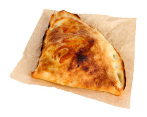 Pizza calzone on tracing paper isolated on white