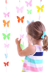 Portrait of little girl on  garlands of butterflies background