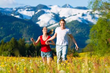 Glückliches Paar lauft auf Wiese vor Bergpanorama