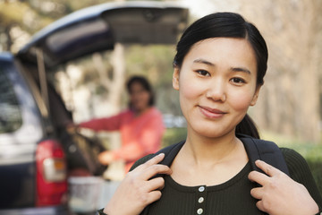 Portrait of girl in front of car on college campus