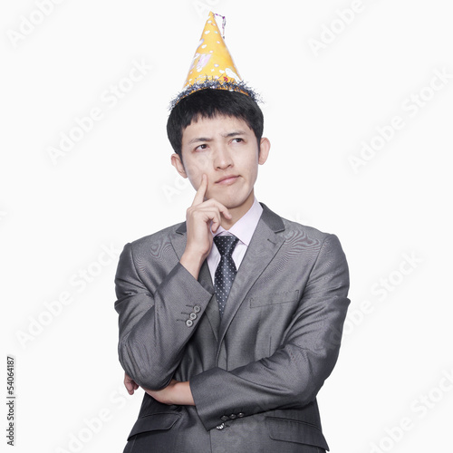Businessman thinking, wearing party hat