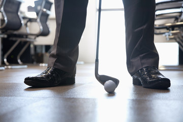 Businessman playing golf in his office, close up on feet