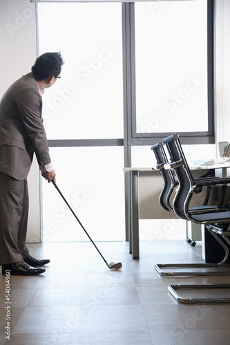 Businessman playing golf in his office