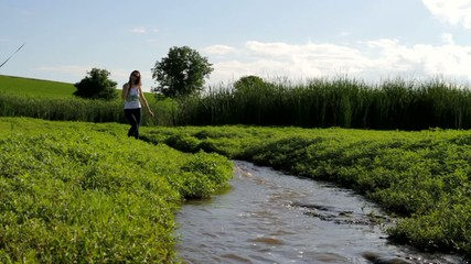 Beautiful Young Woman In Jeans Walking by Water Nature Holiday