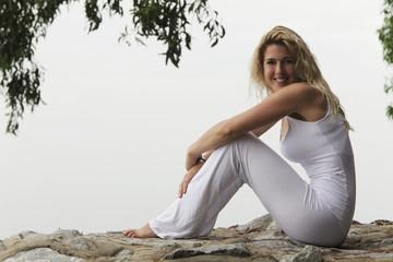 A woman sitting by the seaside in sportwear