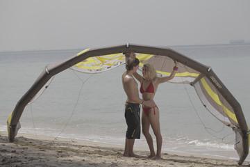 A couple on the beach in swimwear, kitesurfing