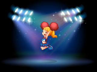 A cheerleader jumping in the middle of the stage