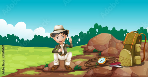 A boy wearing a hat sitting on a rock