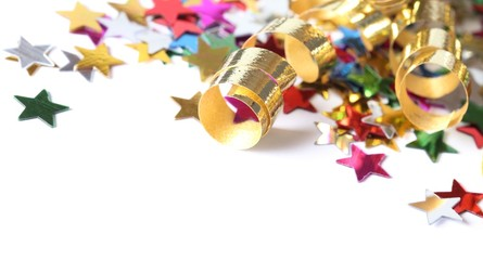 Golden streamers and confetti stars on white background.