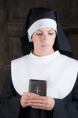 Nun with Bible looking down