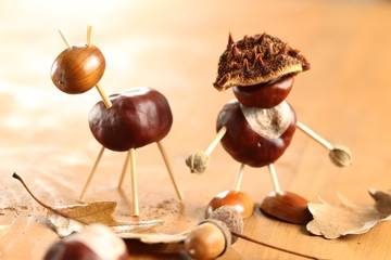 Chestnut and acorn figurines on wooden table