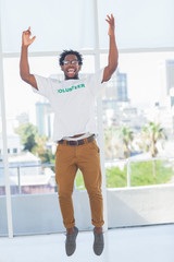 Man jumping with volunteer tshirt then raising his arms
