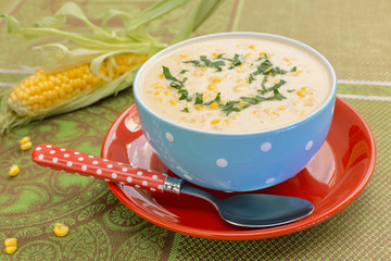 Cream of corn soup in blue bowl with fresh cob of corn on the si